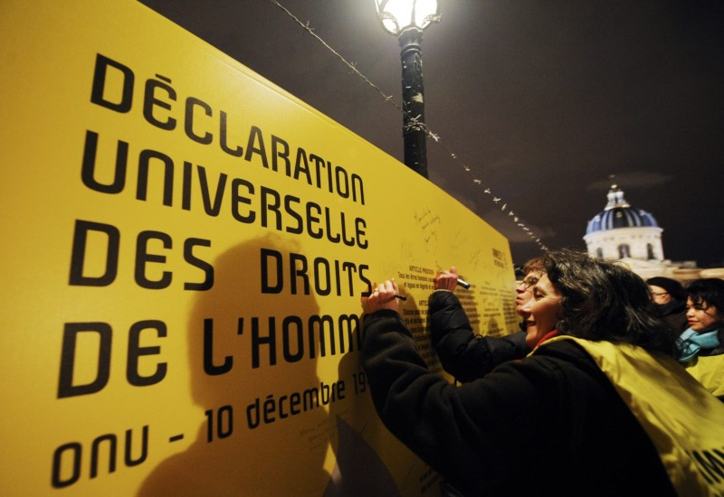 People write on a wall displaying articles of the Universal Declaration of Human Rights, during a rally organized by Amnesty International, on Dec. 10, 2008, in Paris, to commemorate the 60th Declaration by the United Nations.
