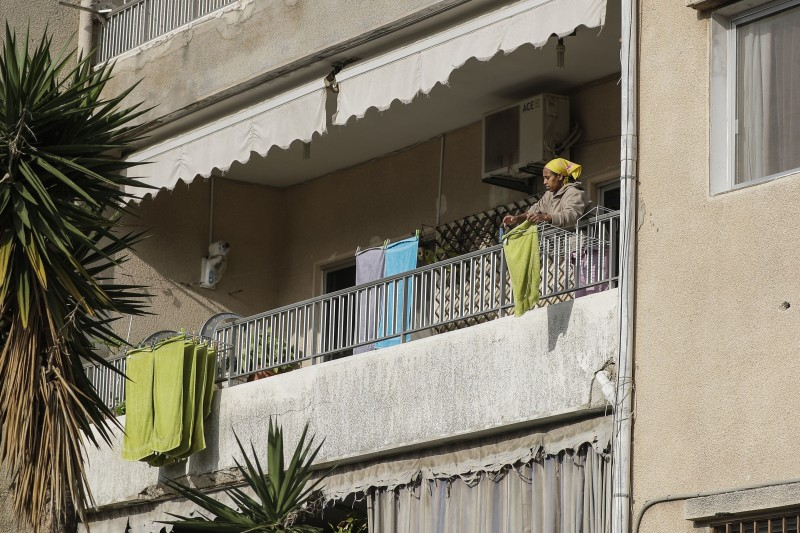An African domestic worker hangs laundry on the balcony of her employer's apartment in the area of Dbayeh north of Beirut on April 24, 2019.