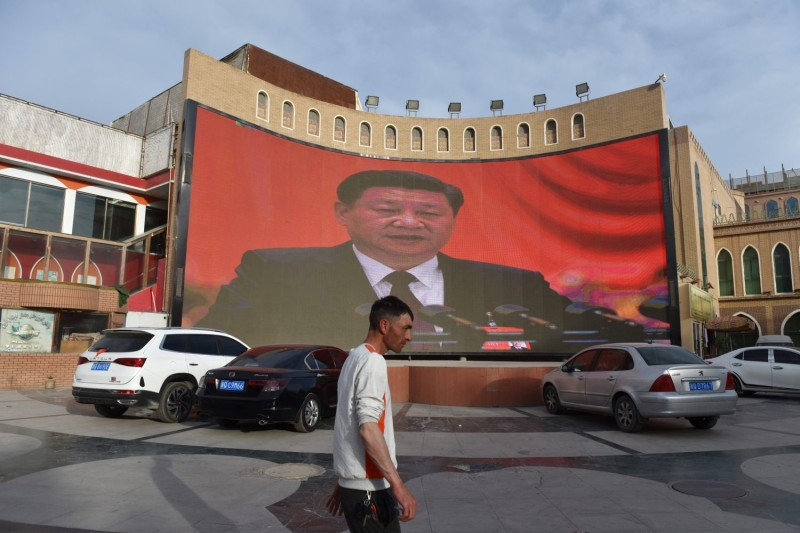 A man walks past a screen showing images of Chinese President Xi Jinping in Kashgar in China's northwest Xinjiang region on June 4, 2019.