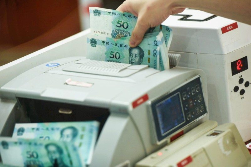 A Chinese bank employee counts new 50-yuan notes with a money counting machine at a bank counter in Hangzhou in China's eastern Zhejiang province on August 30, 2019.