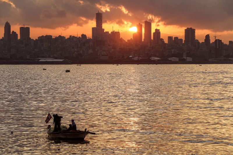 Fishermen cast their nets from a boat at sunset into the Mediterranean sea in the area of Dbayeh, north of the capital Beirut, on Dec. 5, 2019.