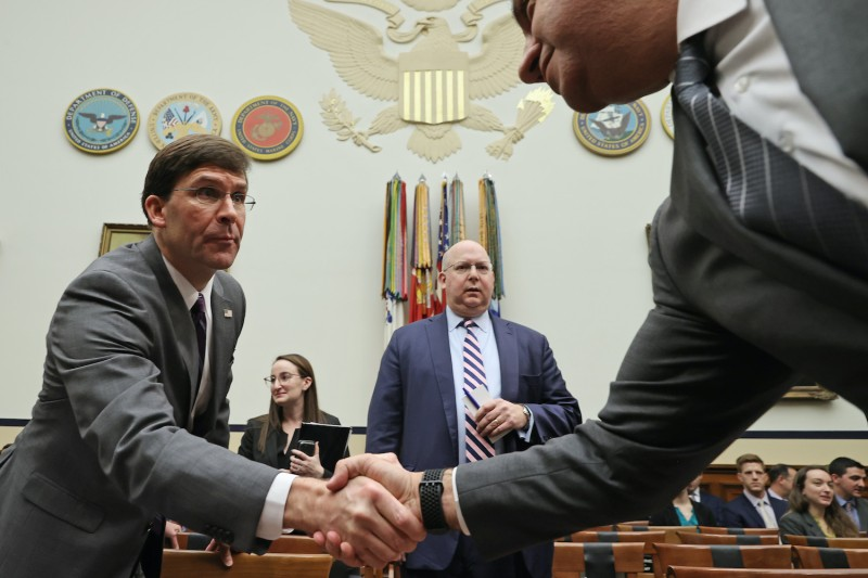 U.S. Defense Secretary Mark Esper (L) greets members of the House Armed Services Committee before testifying to the committee in the Rayburn House Office Building on Capitol Hill February 26 in Washington, DC. Assistant Secretary of Defense for Legislative Affairs Robert Hood is in the background.