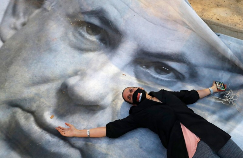 An Israeli protester lies on a banner showing Prime Minister Benjamin Netanyahu at a demonstration against anti-democratic measures to contain the novel coronavirus outbreak in Tel Aviv on April 19.