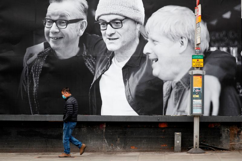 A man wearing a facemask walks past a billboard featuring Britain's Chancellor of the Duchy of Lancaster Michael Gove, Number 10 special advisor Dominic Cummings and Britain's Prime Minister Boris Johnson.