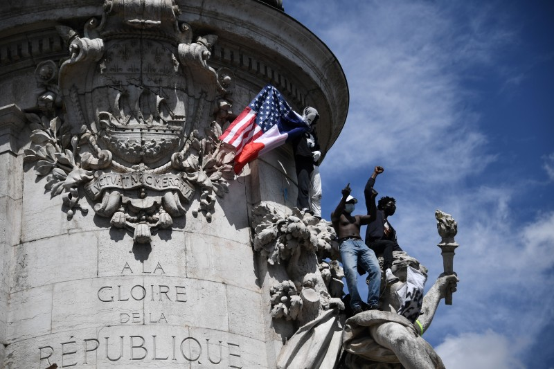 Protesters raise their fist and give the finger from the statue of Marianne on Place de la Republique in Paris on June 13, 2020.