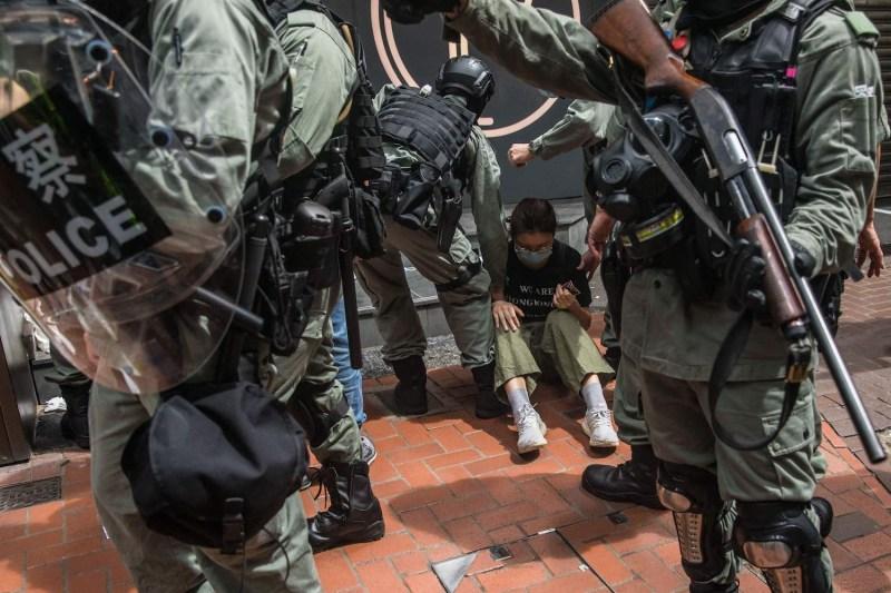 Riot police detain a woman at a rally in Hong Kong.