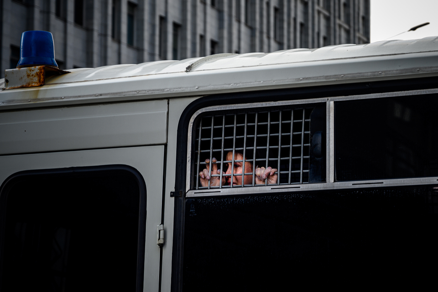 A detained supporter of Ivan Safronov—a former journalist and aide to the head of Russia's space agency Roscosmos—looks out from inside a police bus in central Moscow on July 7. Safronov was detained the same day on charges of treason for divulging state military secrets, authorities said. DIMITAR DILKOFF/AFP via Getty Images