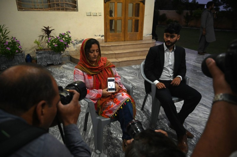 Kaneez Sughra, the wife of abducted Pakistani journalist Matiullah Jan, displays a photograph of her husband on her mobile phone next to her son in Islamabad on July 21.