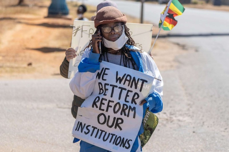 Zimbabwean novelist Tsitsi Dangarembga holds a placard during an anti-corruption protest march along Borrowdale road, on July 31 in Harare.