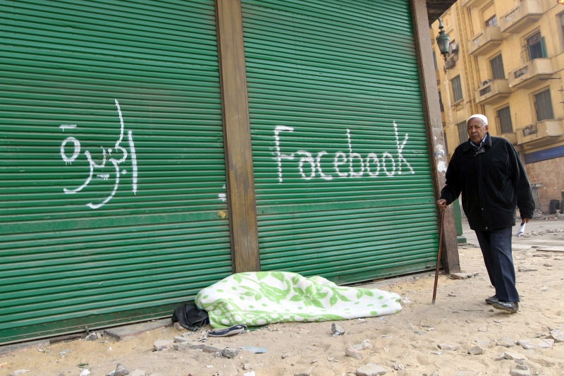 """An Egyptian anti-government demonstrator sleeps on the pavement under spray paint that reads """"Al-Jazeera"""" and """"Facebook"""" at Cairo's Tahrir square on February 7, 2011."""