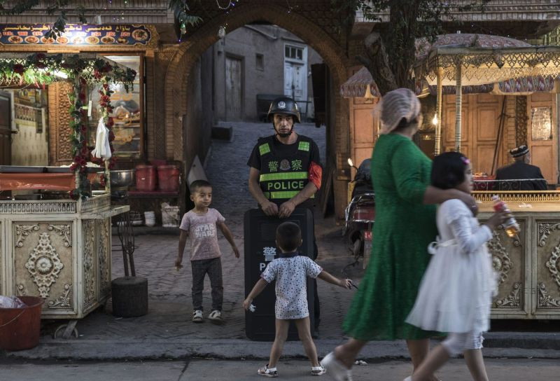 Uighur children joke as they taunt a local police officer in Xinjiang