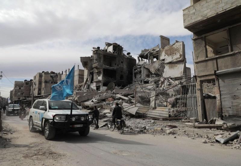 Syrians walk near a humanitarian convoy in Douma, Syria.