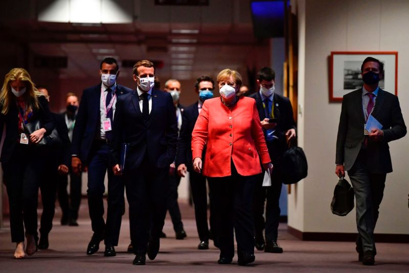 German Chancellor Angela Merkel and French President Emmanuel Macron arrive for a joint press conference at the end of the European summit at the European Union headquarters in Brussels on July 21.