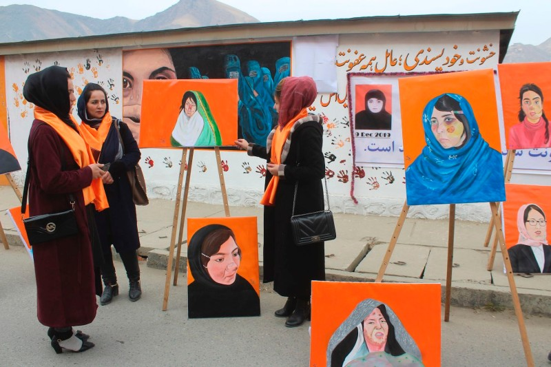 Attendees stand next to portraits of women who suffered violence at an exhibition in support of women in Afghanistan, in Faizabad, Badakhshan province, on Dec. 9, 2019.