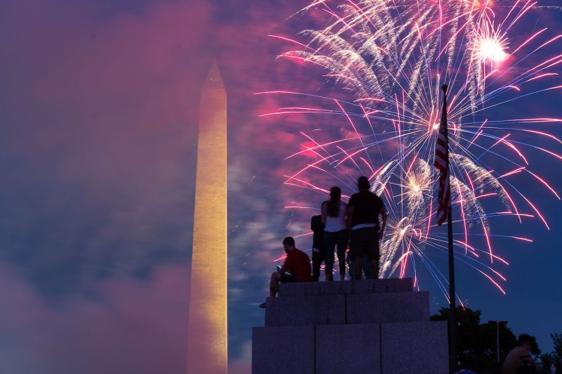 Spectators sit on top of a pillar at the World War II Memorial in the National Mall as fireworks explode in Washington, D.C., on July 4.
