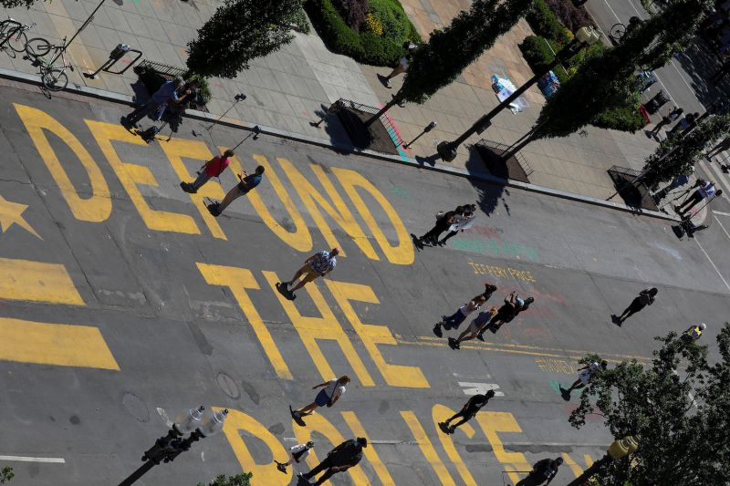 "People walk down 16th Street after ""Defund The Police"" was painted on the street near the White House in Washington, D.C., on June 8."