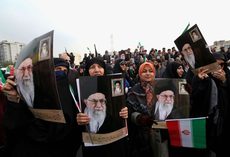 Iranian women holding national flags and pictures of Iran's supreme leader, Ayatollah Ali Khamenei, take part a pro-government demonstration in Tehran on Nov. 25, 2019.
