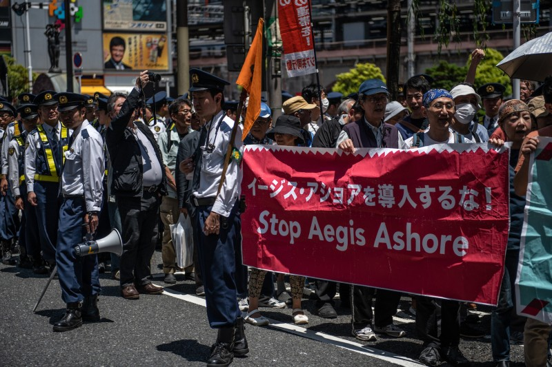 People hold a banner protesting against U.S.-developed Aegis Ashore missile interceptor systems during a demonstration against a forthcoming state visit by U.S. President Donald Trump to Japan in Tokyo on May 25, 2019.