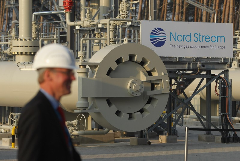A man wearing a hard hat walks by the central facility where the Nord Stream Baltic Sea gas pipeline reaches Western Europe in Lubmin, Germany, on Nov. 8, 2011.