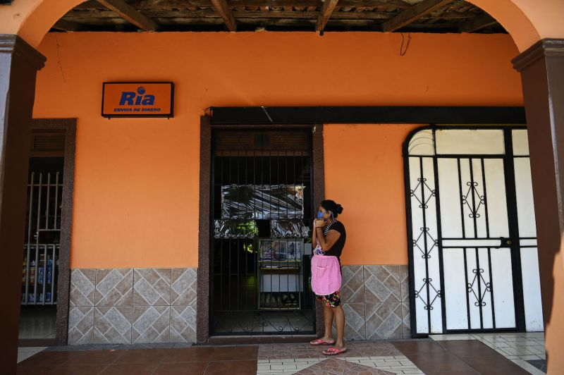 A woman waits outside a U.S. remittance collection agency in San Isidro, El Salvador, on June 10.