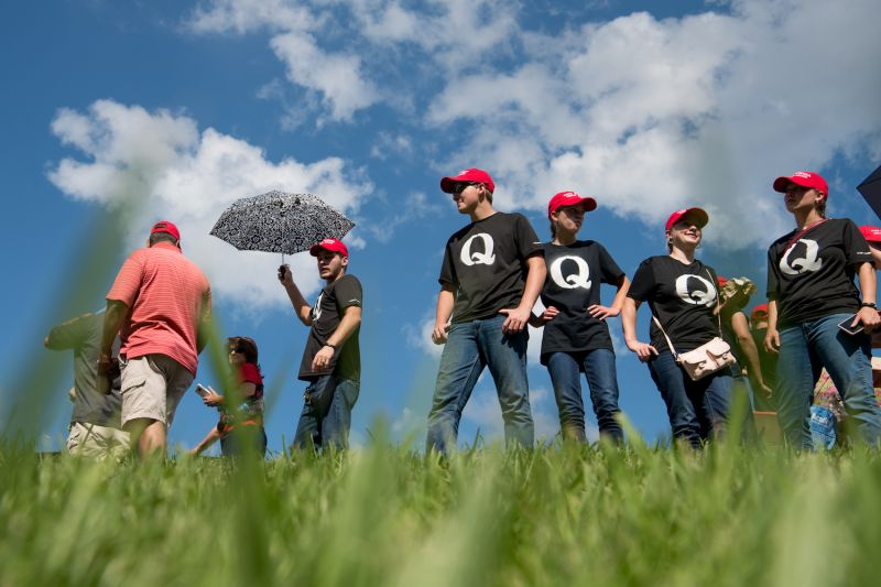 """Supporters of U.S. President Donald Trump wearing """"QAnon"""" t-shirts wait in line before a campaign rally at Freedom Hall in Johnson City, Tennessee, on Oct. 1, 2018."""
