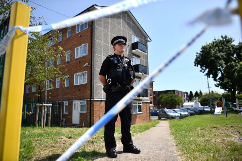 A police officer stands guard outside a cordoned-off block of apartments where the suspect in a multiple stabbing incident lived in Reading, west of London, on June 23.