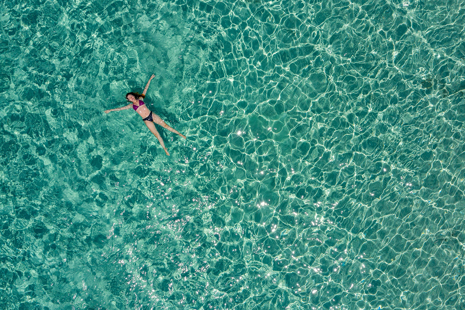 A woman relaxes on the sea off the small island of Chrysi, south of Crete, Greece, on July 26. ARIS MESSINIS/AFP via Getty Images