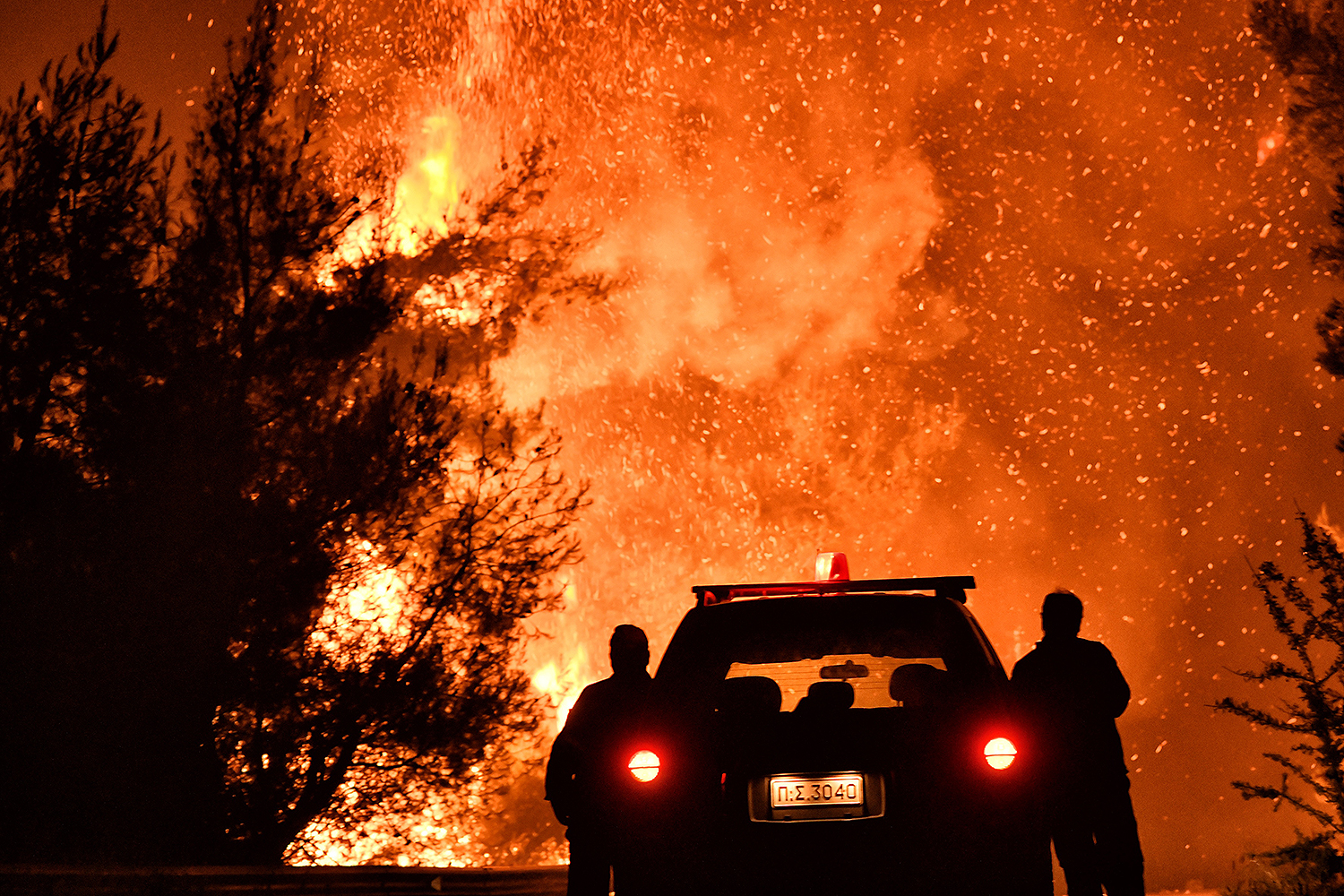 Firefighters stand near a pine forest wildfire fanned by strong winds near the village of Athikia, Greece, on July 22. VALERIE GACHE/AFP via Getty Images