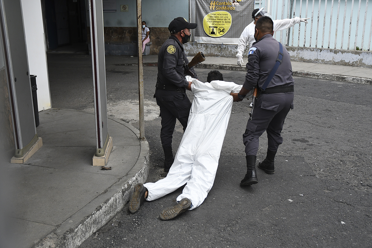 Penitentiary system guards carry an inmate with symptoms related to the coronavirus to the COVID-19 unit of San Juan de Dios Hospital in Guatemala City on July 13. JOHAN ORDONEZ/AFP via Getty Images