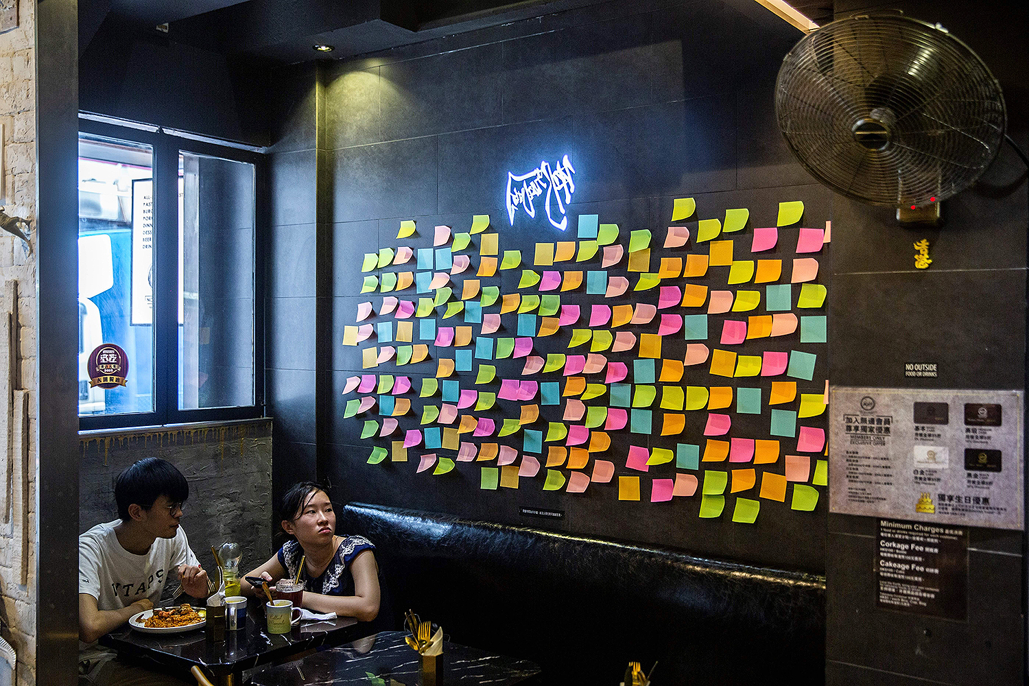 Customers sit near blank notes on a wall inside a pro-democracy restaurant in Hong Kong on July 3—a response to a new national security law introduced in the city that makes political views, slogans, and signs that advocate for Hong Kong's independence or liberation illegal. ISAAC LAWRENCE/AFP via Getty Images