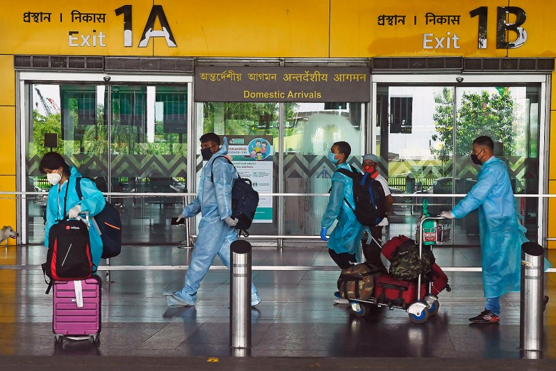 Air passengers wearing protective suits walk out of the arrival lounge of Netaji Subhas Chandra Bose International Airport in Kolkata, India, on July 6.