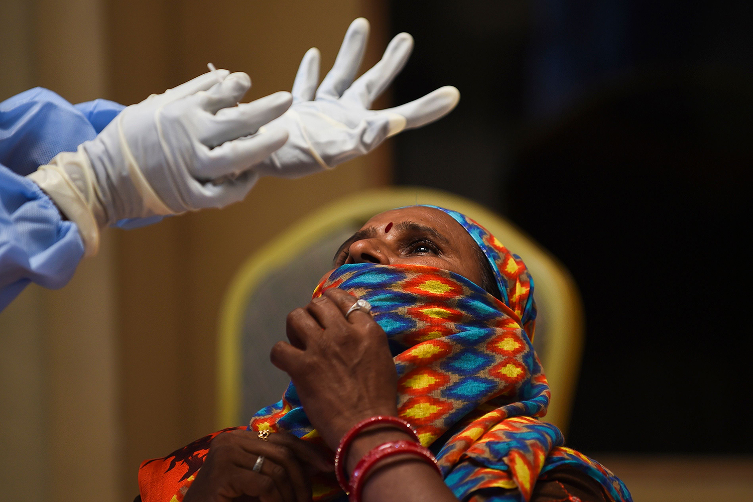 A health worker prepares to take a swab sample from a passenger at Ranip Bus Terminus in Ahmedabad, India, on July 13. SAM PANTHAKY/AFP via Getty Images