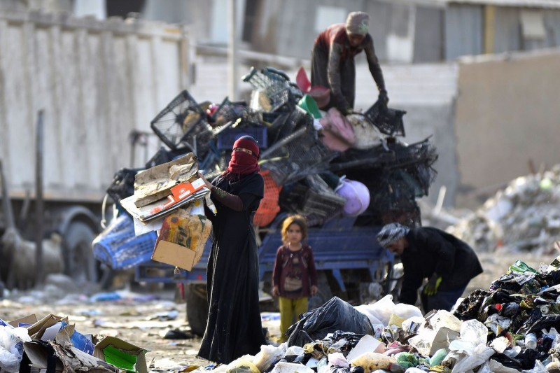 People collect recyclable items at a landfill, to be sold for extra income, in Iraq