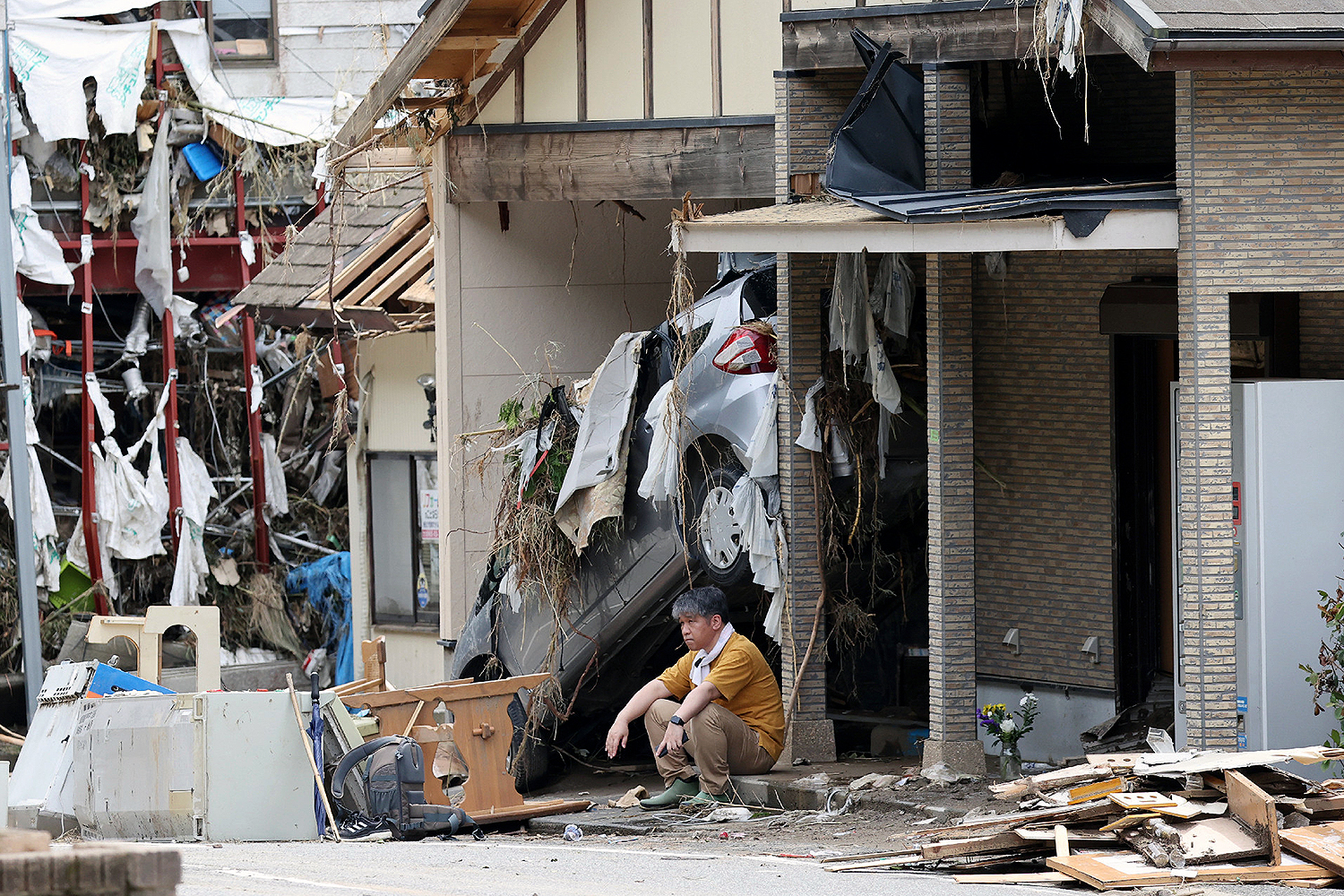 A man sits outside the house of his aunt, who died from flooding of the Kuma River in Yatsushiro, Kumamoto Prefecture, Japan, on July 8. STR/JIJI PRESS/AFP via Getty Images