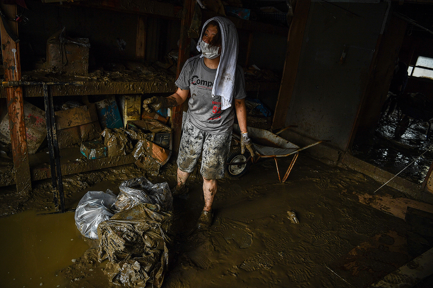 A resident clears mud from a home in Hitoyoshi, Japan, on July 10 after heavy rains, flooding, and landslides devastated the region. CHARLY TRIBALLEAU/AFP via Getty Images