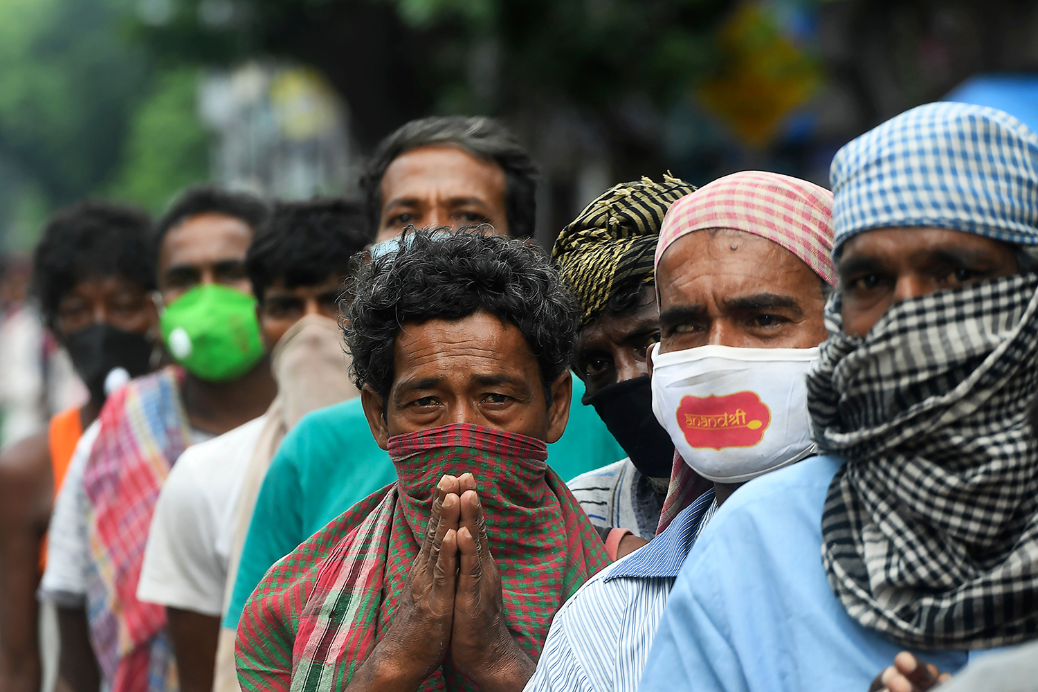 Homeless people wait in a line to collect food on the side of a road in Kolkata, India, on July 25. DIBYANGSHU SARKAR/AFP via Getty Images