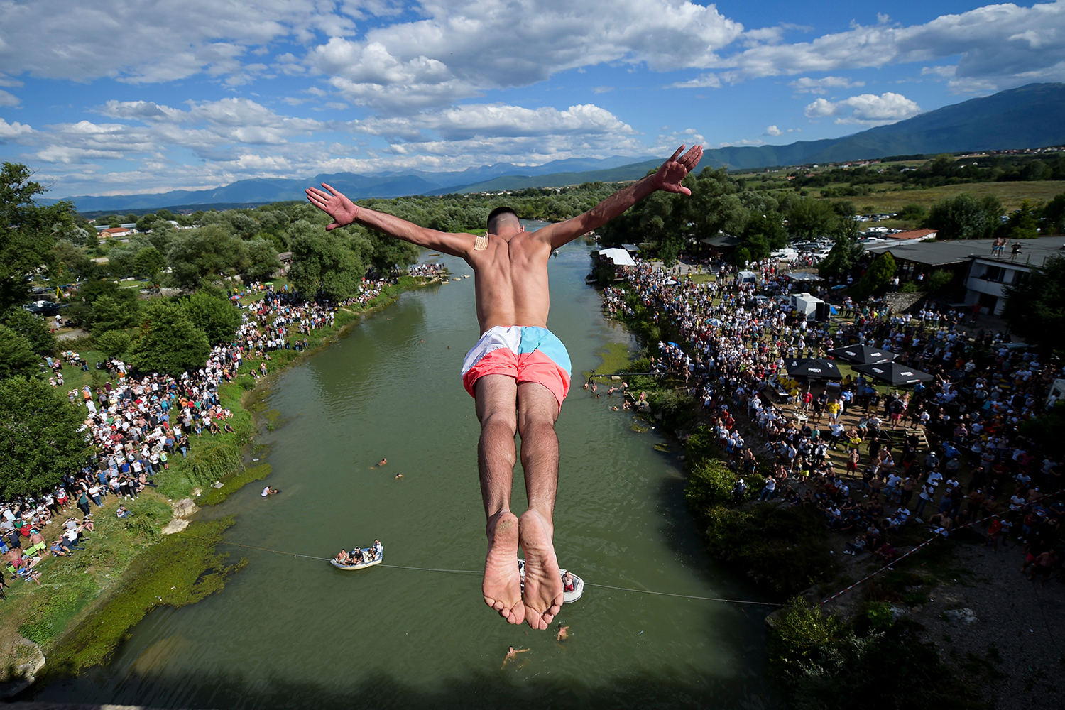 A diver jumps from the 72-foot-high Fshajt Bridge, or Sacred Bridge, near the town of Gjakova, Kosovo, on July 19 as sign of protest after police canceled the 70th annual high diving competition because spectators failed to follow social distancing rules. ARMEND NIMANI/AFP via Getty Images