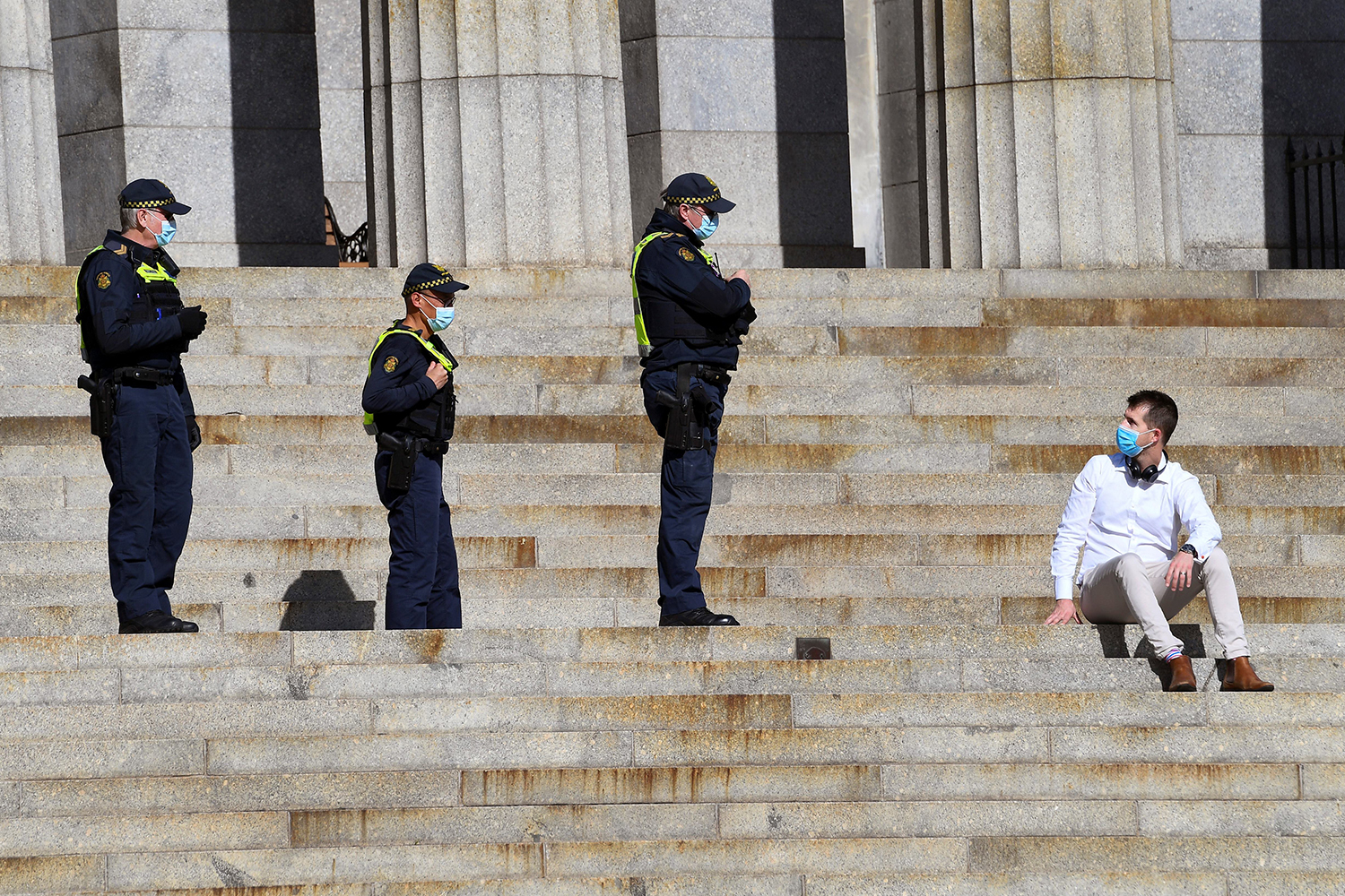 In the midst of its strict coronavirus lockdown, officers speak to a man sitting on the steps of the Shrine of Remembrance in Melbourne, Australia, on July 31. WILLIAM WEST/AFP via Getty Images
