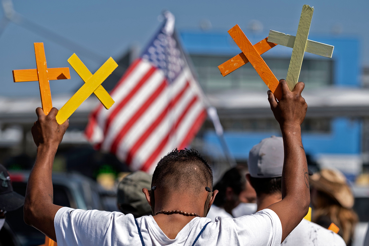 A deported migrant holds up crosses during a demonstration against U.S. President Donald Trump's migration policies at the San Ysidro Port of Entry in Tijuana, Baja California state, Mexico, on July 8. GUILLERMO ARIAS/AFP via Getty Images