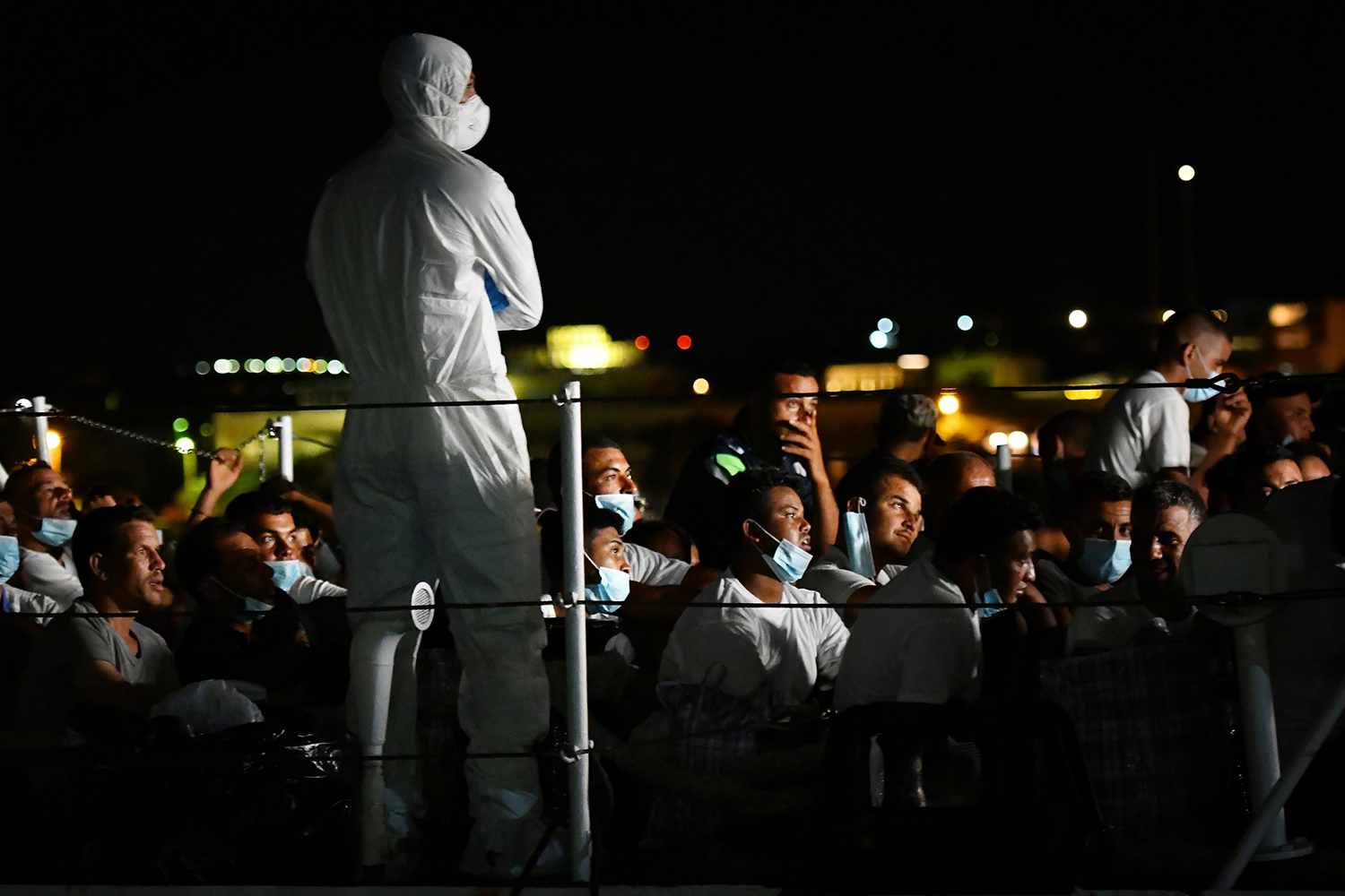 Migrants wait onboard a coast guard ship in the harbor the Pelagie Island of Lampedusa in Italy on July 30. ALBERTO PIZZOLI/AFP via Getty Images