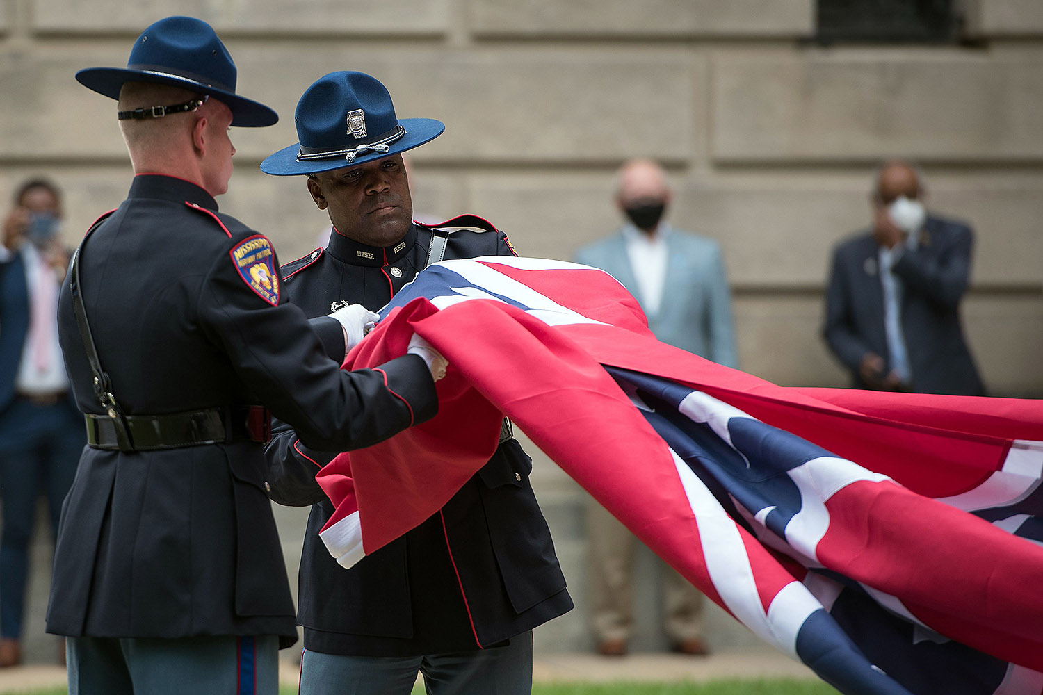 Members of the Mississippi Highway Safety Patrol Honor Guard retire the state flag outside the capitol building in Jackson, Mississippi, on July 1. The flag, the last in the United States to feature a Confederate emblem, was permanently retired. RORY DOYLE/AFP via Getty Images