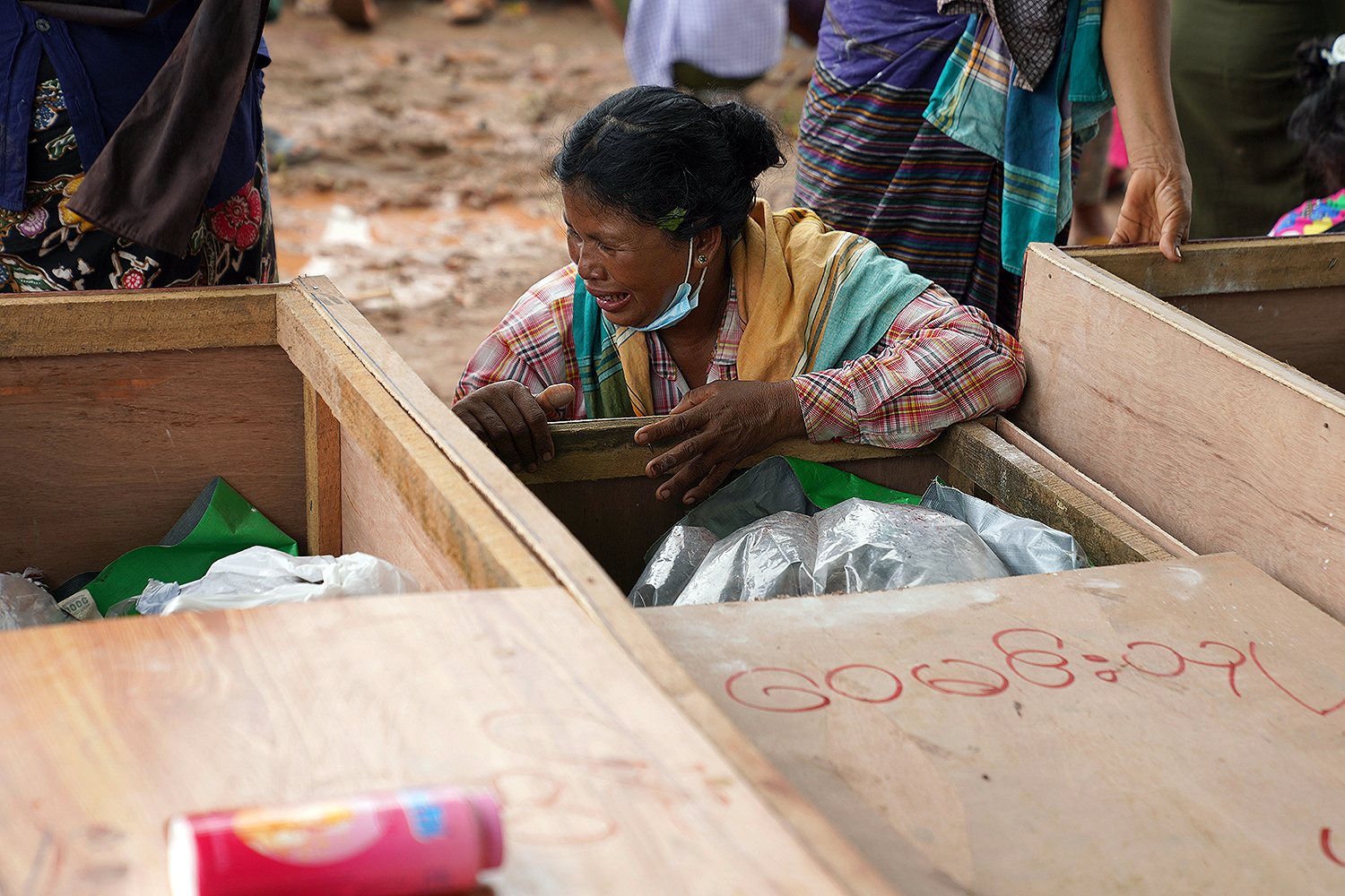 A woman grieves over the body of a miner during a funeral ceremony near Hpakant in Kachin state, Myanmar, on July 3. More than 160 people were killed when torrential rains triggered a landslide at a jade mining site in northern Myanmar. ZAW MOE HTET/AFP via Getty Images