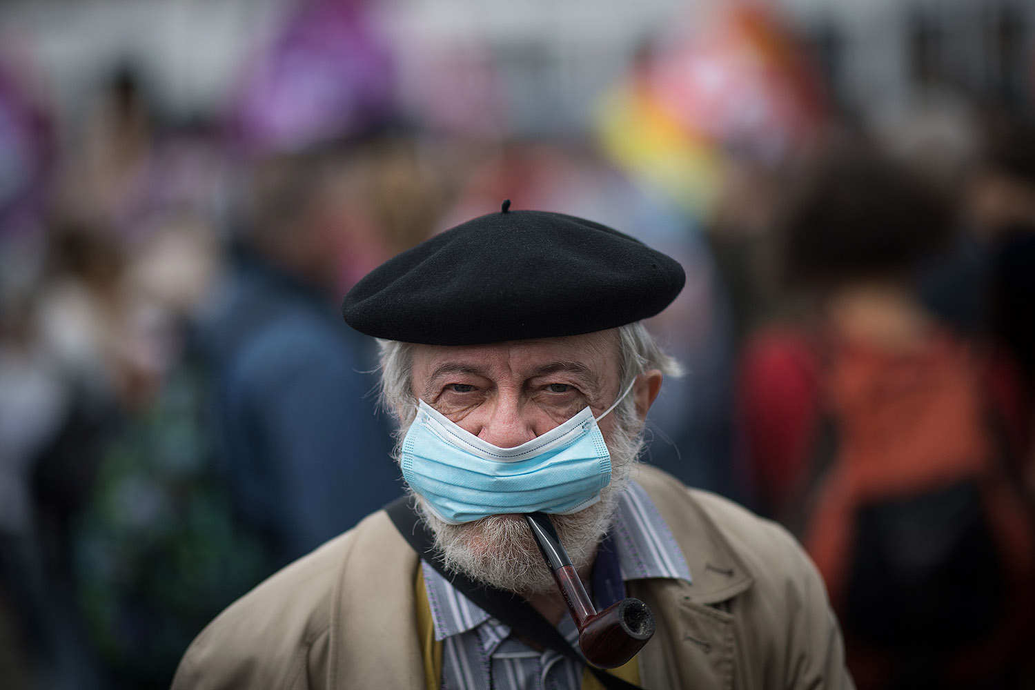 A man smokes a pipe while wearing a face mask during a demonstration in Nantes, France, on June 30 as part of a nationwide day of protests to demand better working conditions for health care workers. LOIC VENANCE/AFP via Getty Images