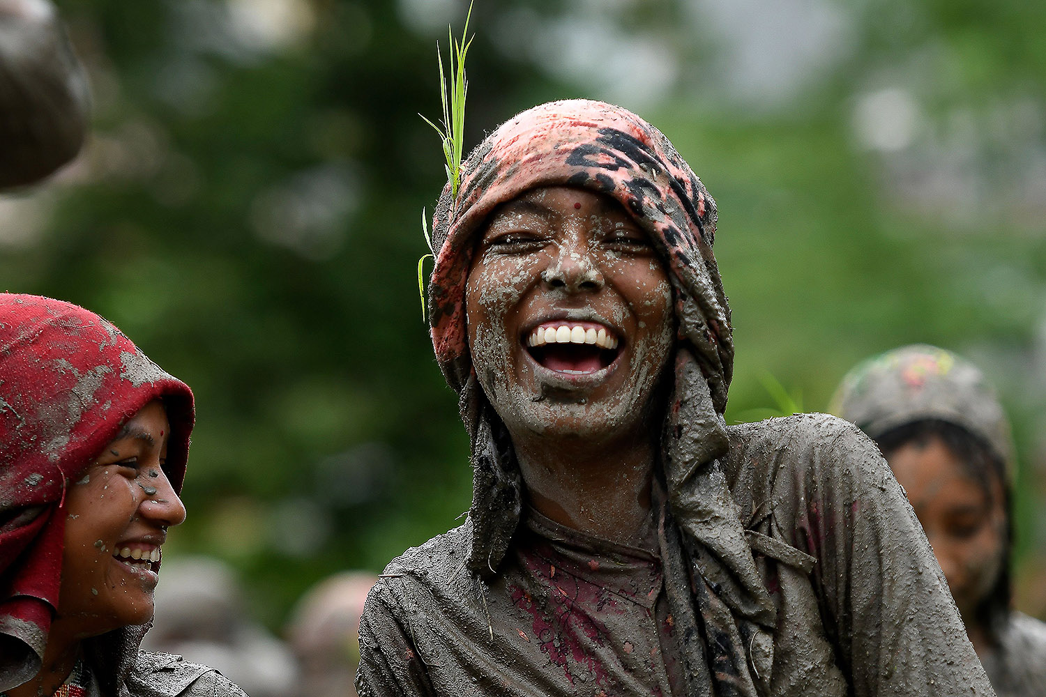 A woman smiles in a rice paddy field during National Paddy Day—which marks the start of the annual rice planting season—in Tokha village on the outskirts of Kathmandu, Nepal, on June 29. PRAKASH MATHEMA/AFP via Getty Images