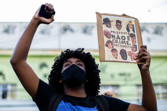 """Um manifestante segura uma placa que diz """"Pele negra não é crime. Racismo é!"""" num protesto nas ruas de São Gonçalo, Brasil, em 5 de junho. Cerca de 300 pessoas gritaram slogans contra o governo do presidente Jair Bolsonaro e protestaram contra a morte do americano George Floyd e do adolescente João Pedro Mattos Pinto."""