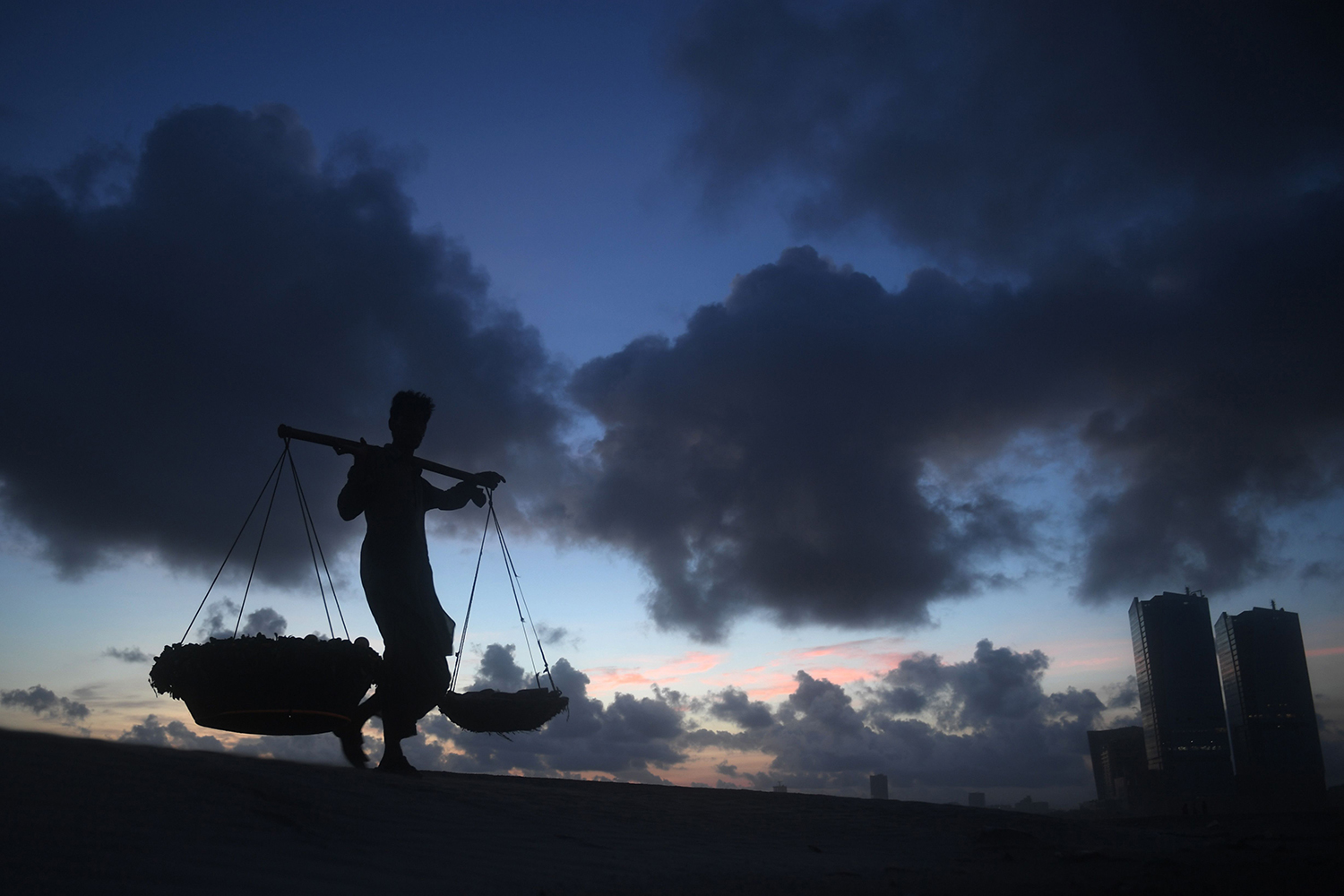 A fruit vendor walks with his wares at Sea View Beach in Karachi, Pakistan, on July 19. ASIF HASSAN/AFP via Getty Images