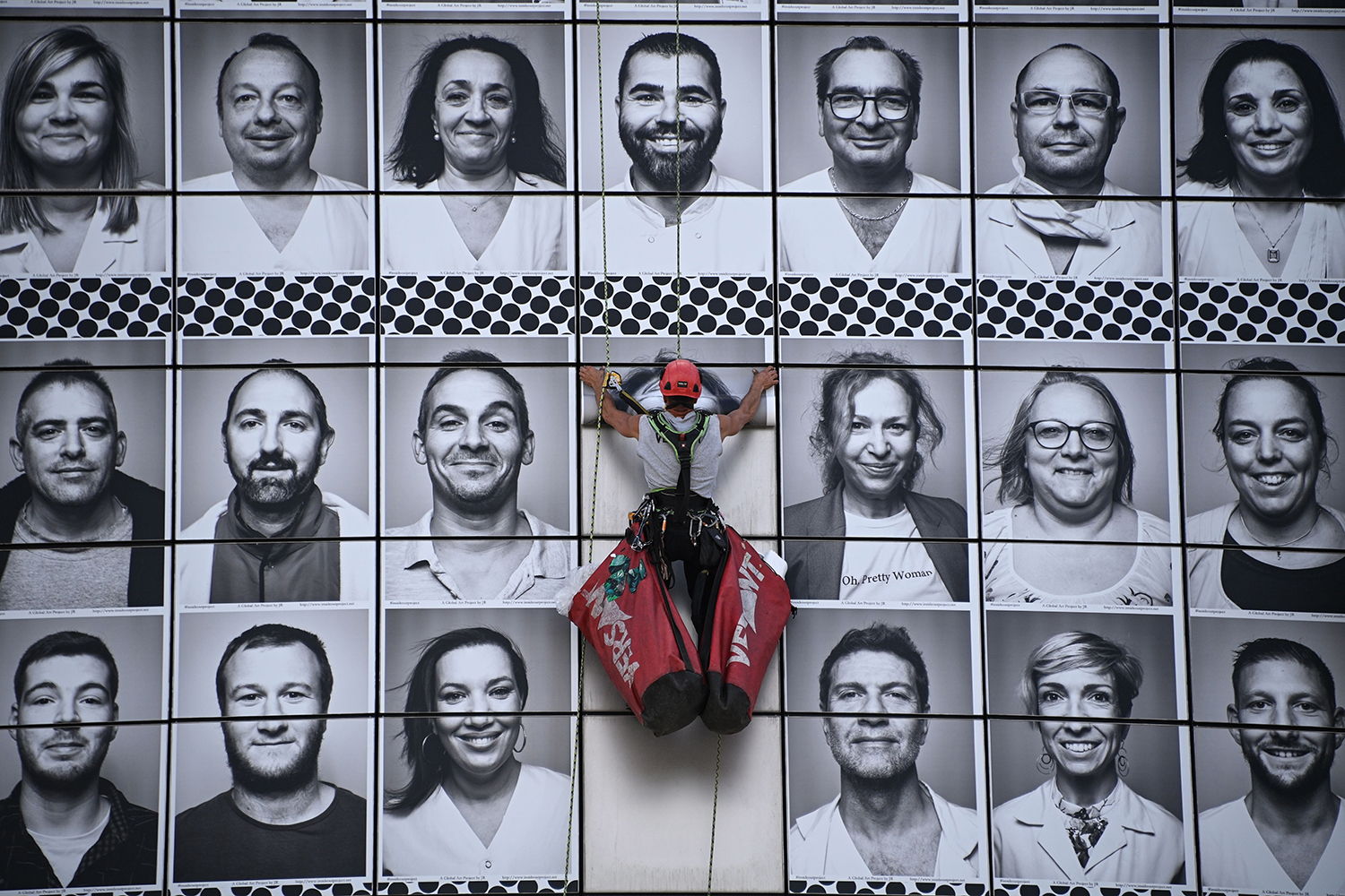 A worker pastes portraits of health care workers on the facade of the Opera Bastille in Paris on July 8—an initiative to pay tribute to caregivers on the front lines of the COVID-19 pandemic. ANNE-CHRISTINE POUJOULAT/AFP via Getty Images