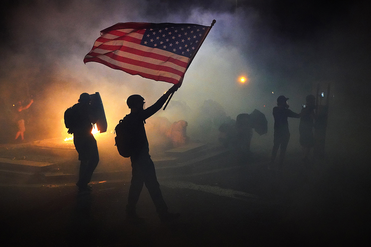 A protester waves an American flag while walking through tear gas fired by federal officers during a protest in front of the Mark O. Hatfield U.S. Courthouse in Portland, Oregon, on July 21. Nathan Howard/Getty Images