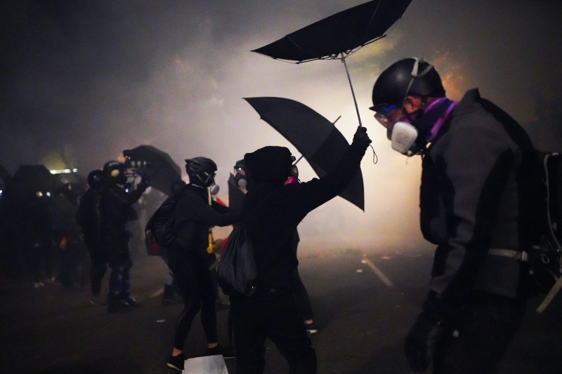 Protesters use umbrellas to block pepper balls while clashing with federal officers at the Mark O. Hatfield U.S. Courthouse on July 22, 2020 in Portland, Oregon.