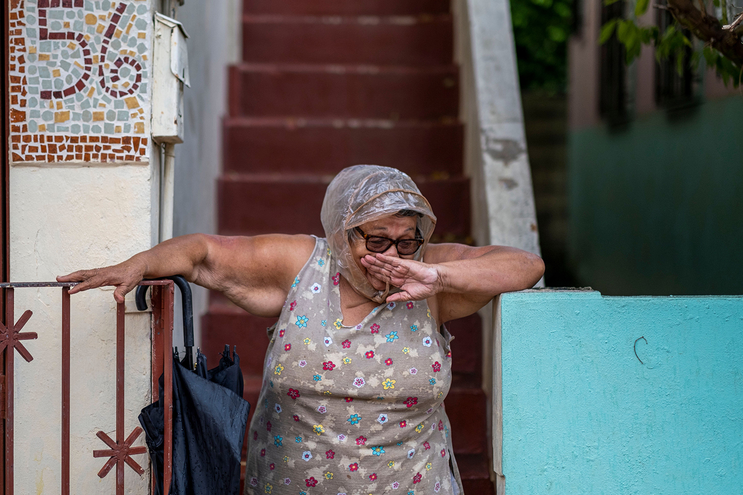 A woman stands on her porch in Mayaguez, Puerto Rico, on July 30 after Tropical Storm Isaias blew through the area. RICARDO ARDUENGO/AFP via Getty Images